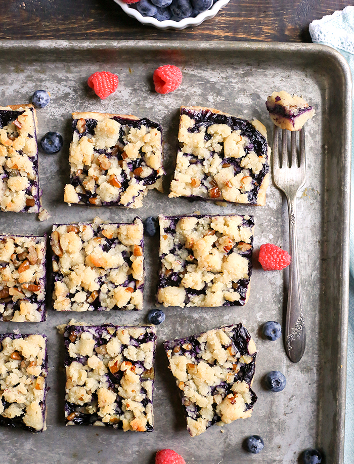 These Paleo Blueberry Pie Crumb Bars are simple to make and so delicious. A shortbread crust, thick layer of blueberries, and a crumble topping. These layered bars are gluten free, dairy free, vegan, and naturally sweetened.