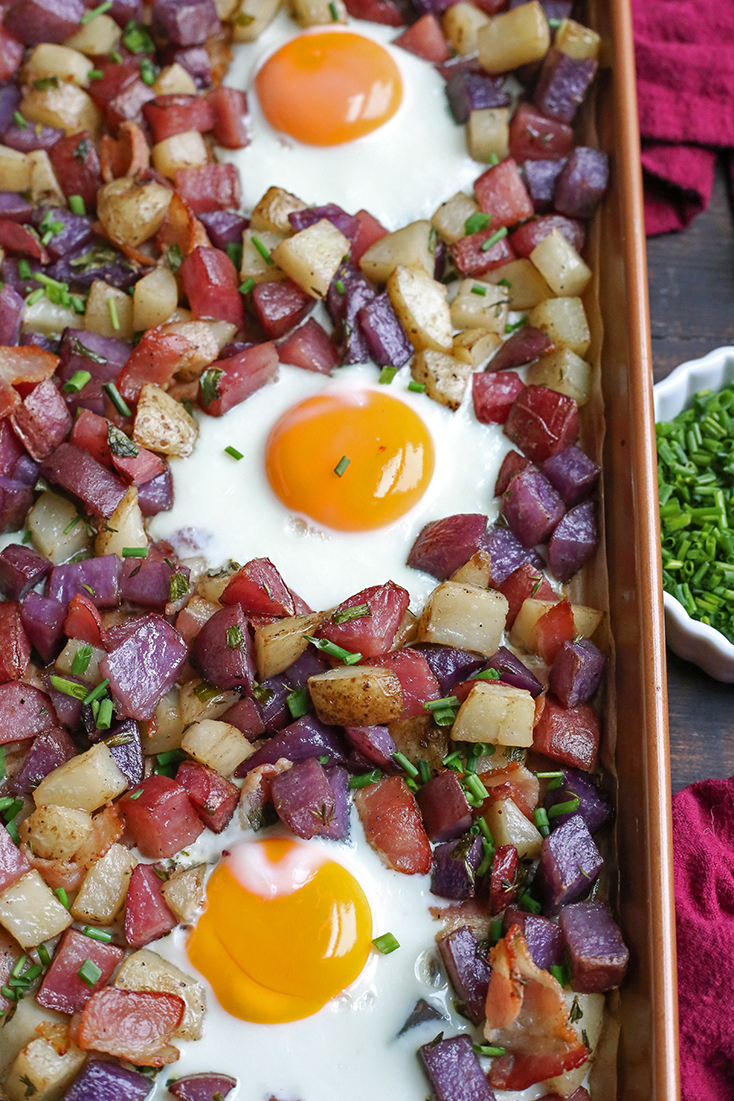 This Paleo Whole30 Sheet Pan Hash and Eggs is so simple to make and delicious! Crispy potatoes, bacon, and perfectly cooked eggs. It's gluten free, dairy free, and low FODMAP.
