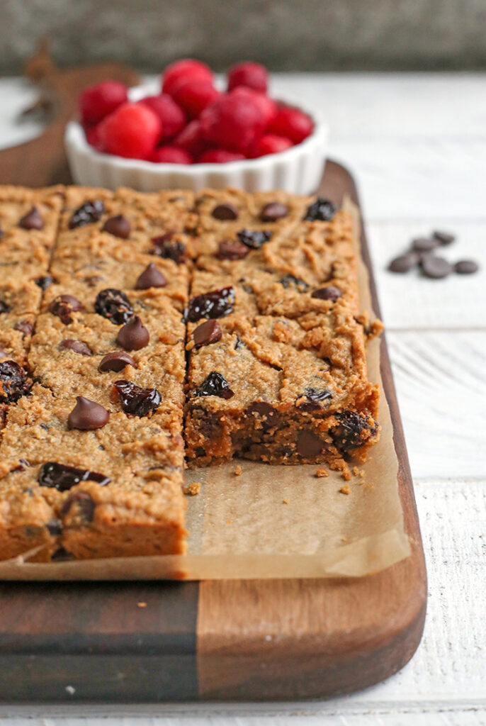 a board with paleo cherry chocolate chips bars on it. One is removed so the inside is showing.