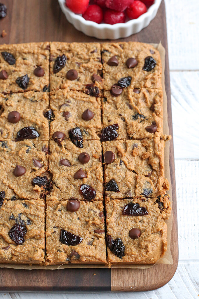 paleo cherry chocolate chips bars on a cutting board, cut into squares