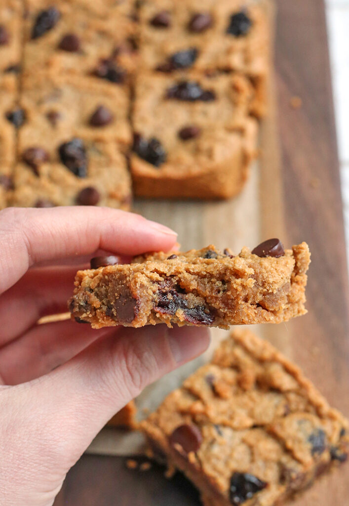 paleo cherry chocolate chip bar being held with a bite taken out of it