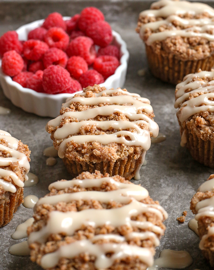 paleo coffee cake muffins on a tray with raspberries