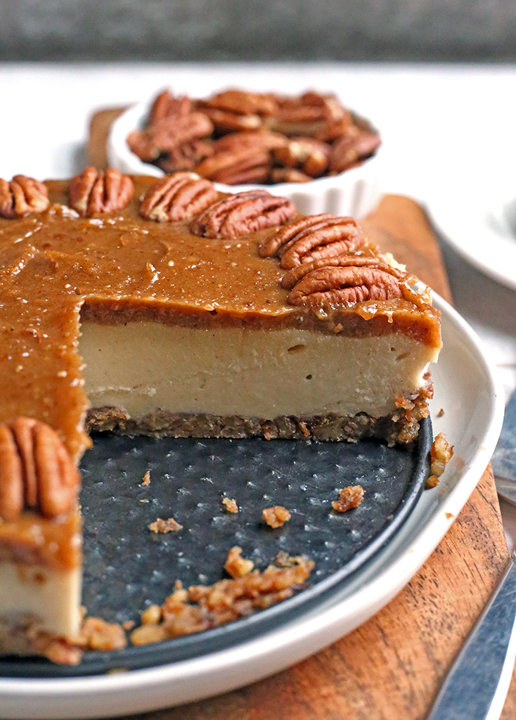 paleo vegan caramel pecan cheesecake with a slice removed, inside is showing