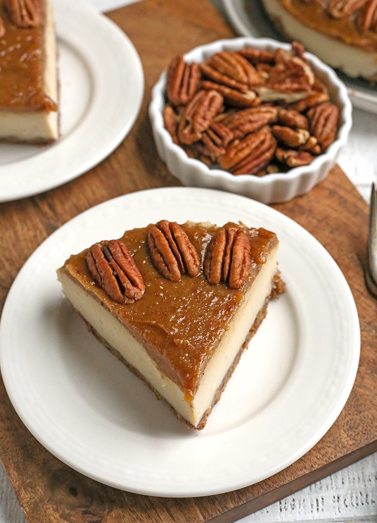 a piece of paleo vegan caramel pecan cheesecake on a plate