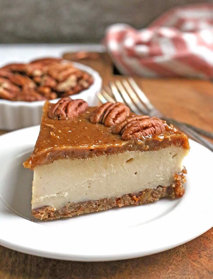 a slice of paleo vegan caramel pecan cheesecake