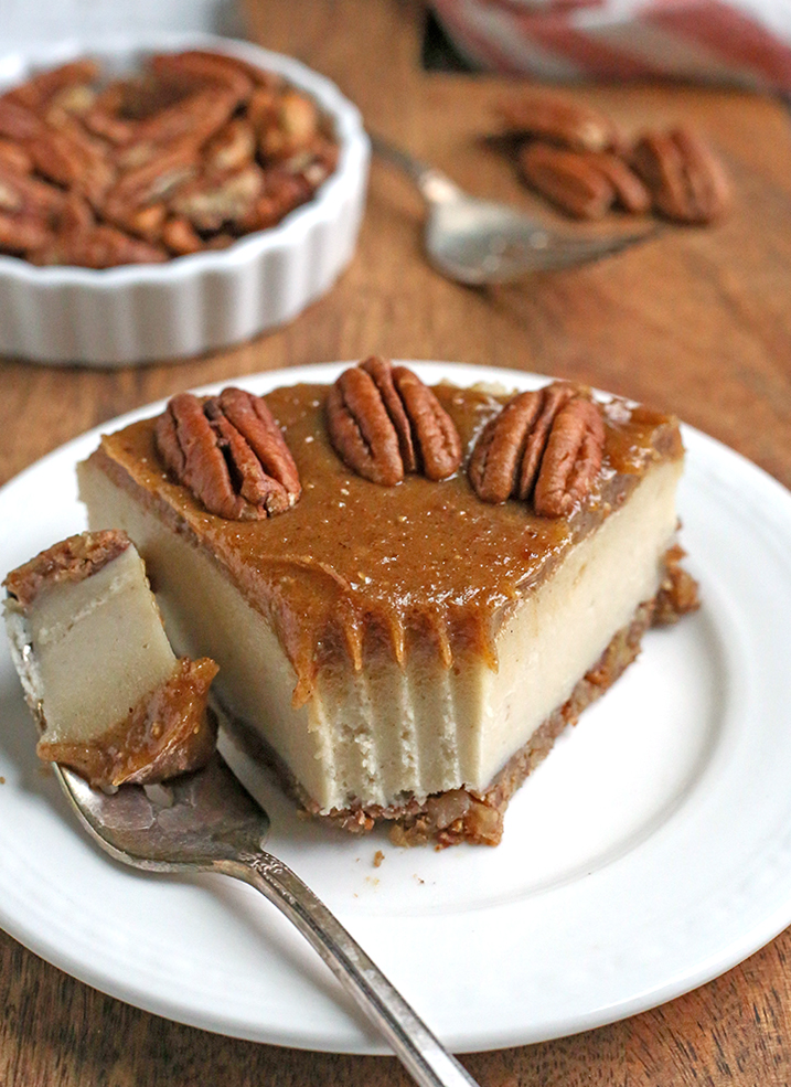 paleo vegan caramel pecan cheesecake with a bite taken out and set to the side