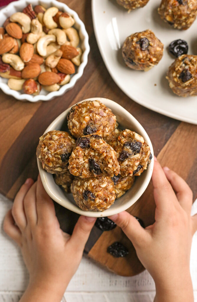 granola bites in a small bowl with two small hands holding it