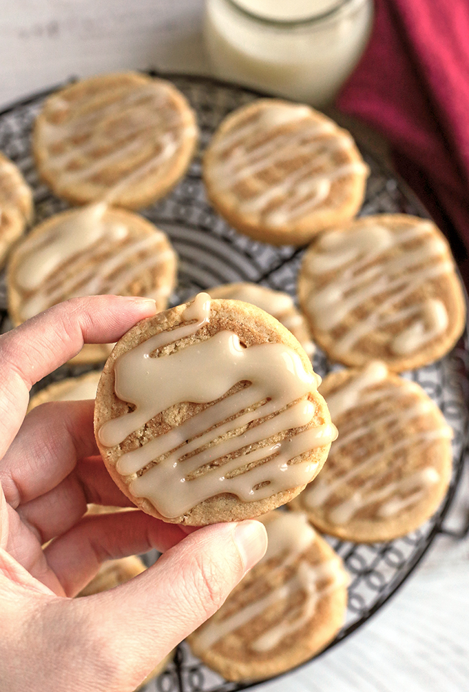 hand holding a paleo cinnamon roll cookie showing the top with icing