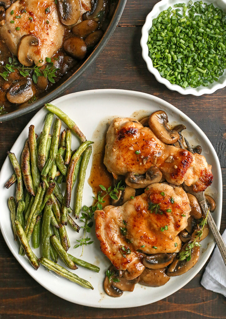 paleo creamy mushroom chicken on a plate with green beans