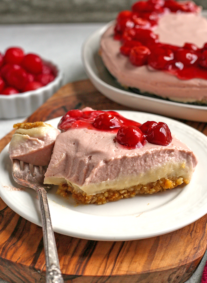 vegan paleo cherry cheesecake with a bite taken out. Bite is on fork next to the slice.