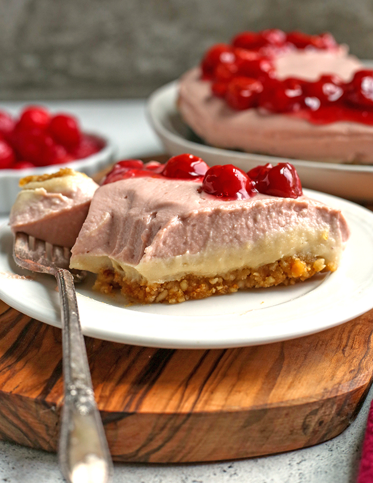 paleo vegan cherry cheesecake slice on a plate with a bite taken out
