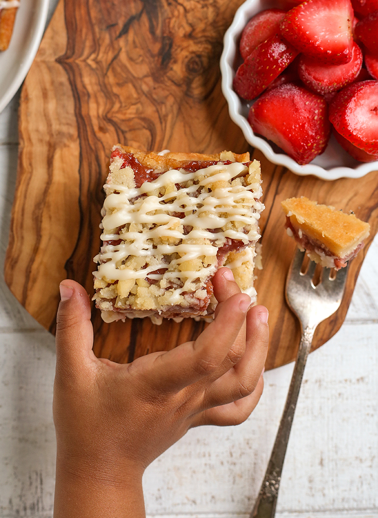 small hand reaching for a paleo strawberry crumb bar