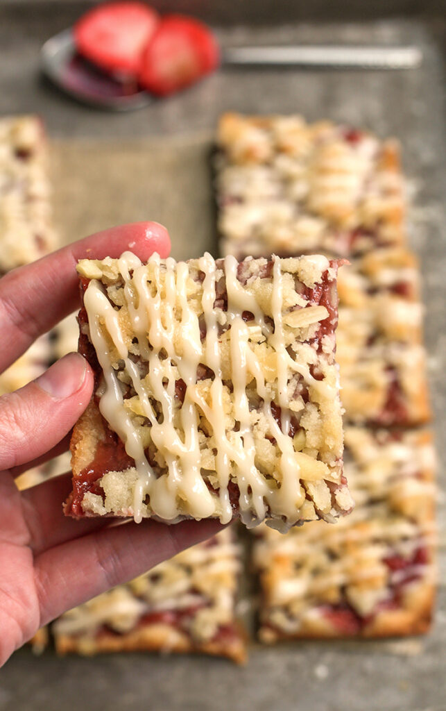 a hand holding a paleo strawberry crumb bars showing the top