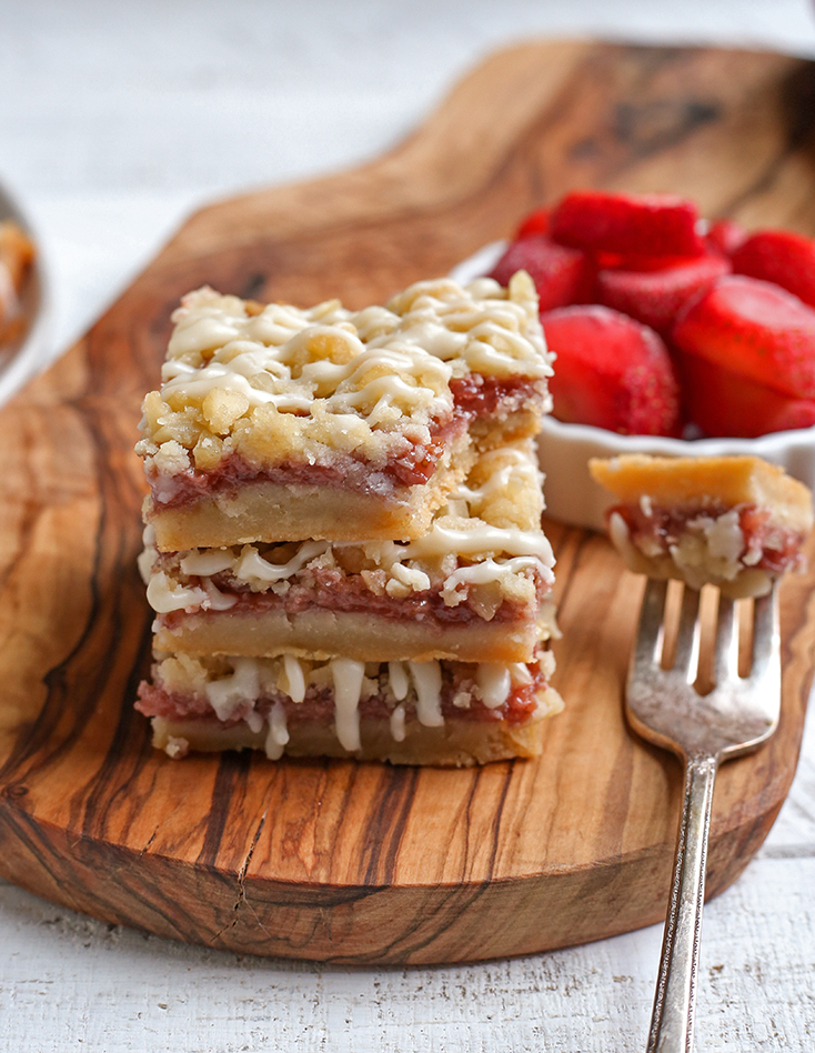 stack of strawberry crumb bars with a bite taken out of one