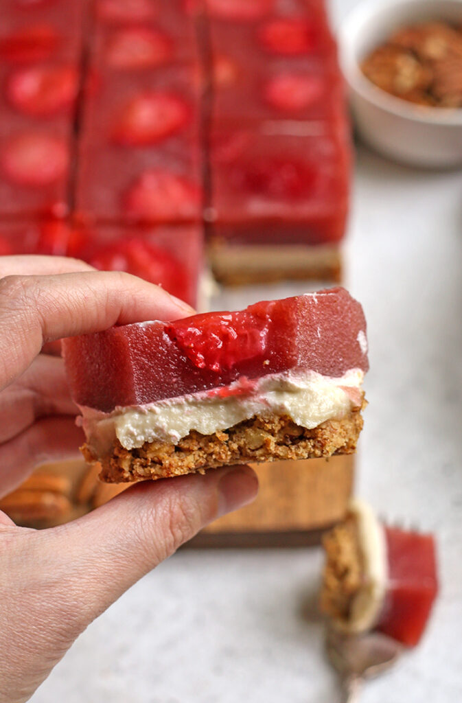 hand holding a piece of paleo strawberry pretzel salad with a bite taken out