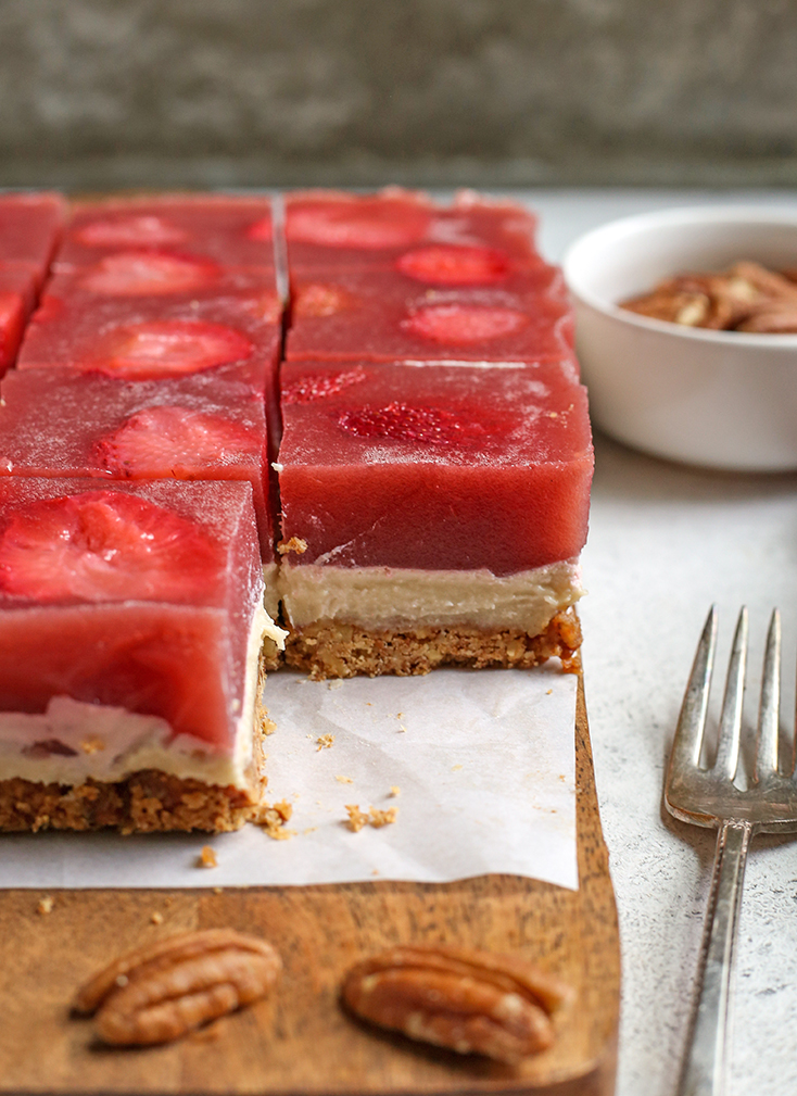 slices of paleo strawberry pretzel salad. One piece removed to show the layers of crust, cream cheese and gelatin.