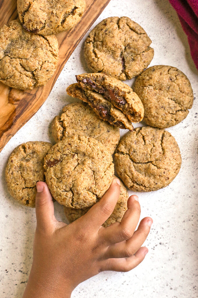 a little hand grabbing a paleo chocolate stuffed cookie