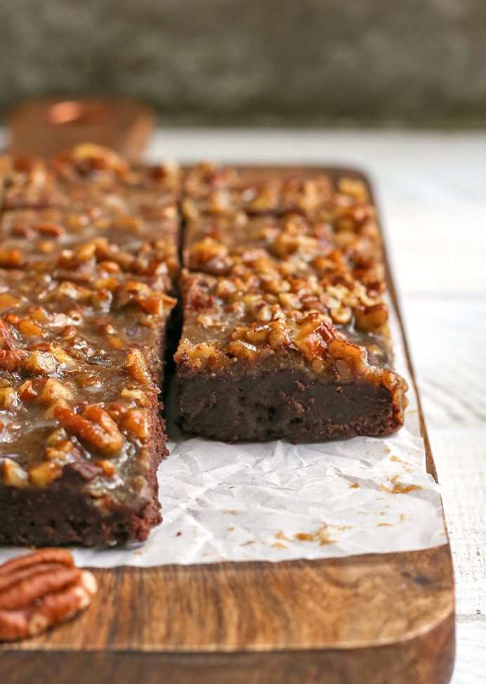 a cutting board with squares of paleo pecan praline brownies on it
