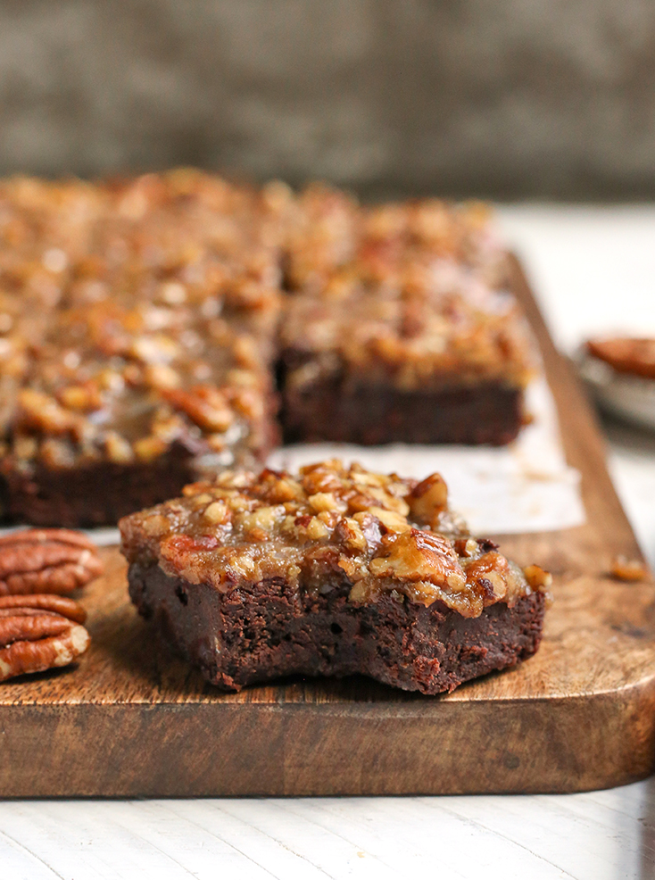 a pecan paleo brownie close up with others behind it
