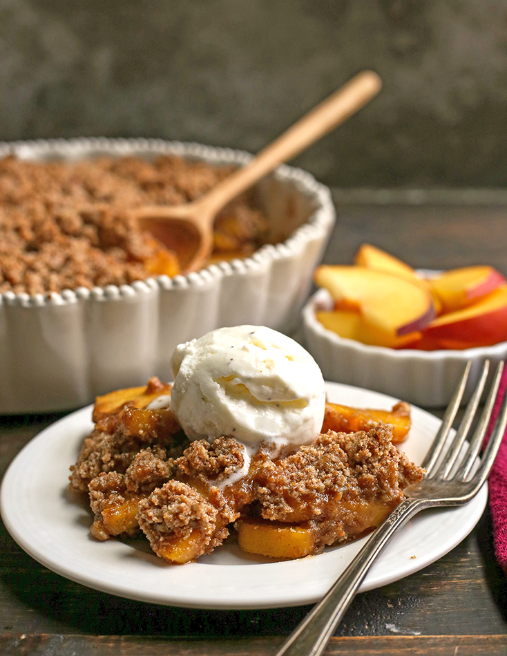 side shot of paleo vegan peach crisp on a plate with ice cream