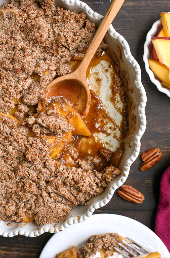 paleo vegan peach crisp in a pan with a scoop taken out