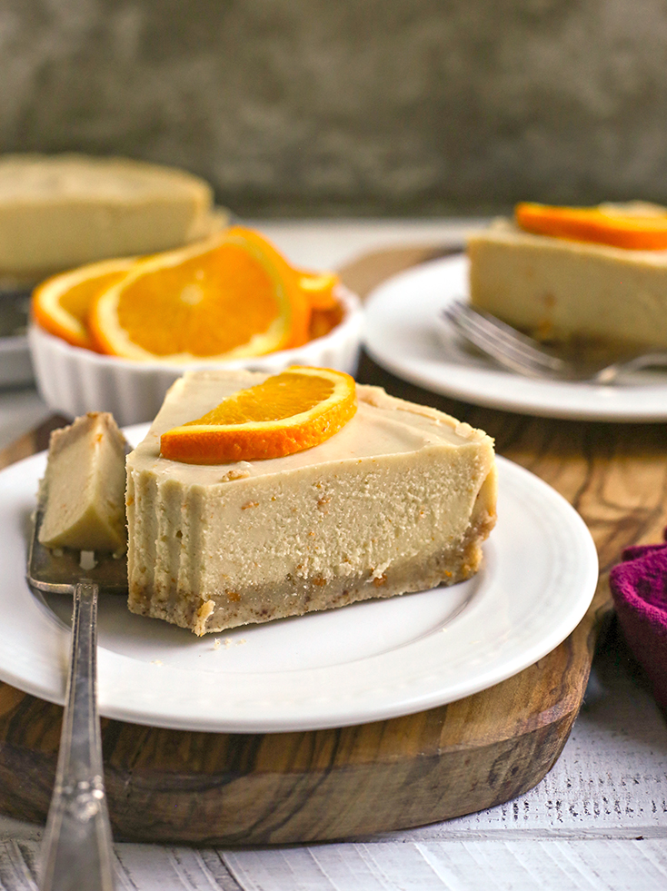 paleo vegan orange creamsicle cheesecake with a bite taken out