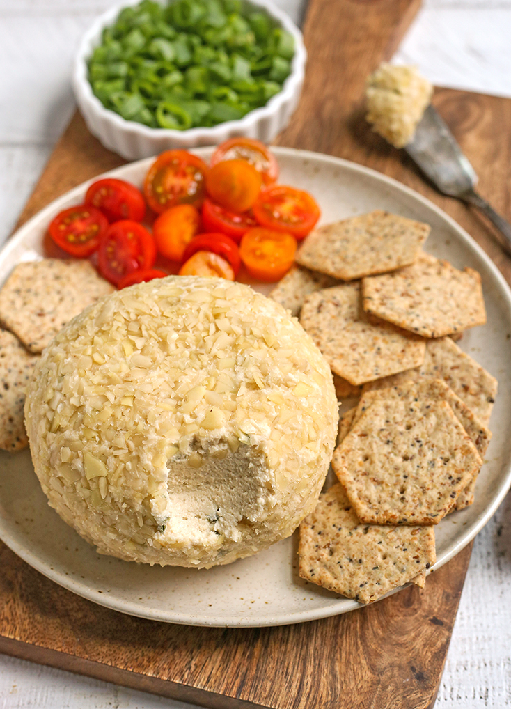 vegan paleo cheeseball on a plate with crackers, with a bite out of the cheeseball