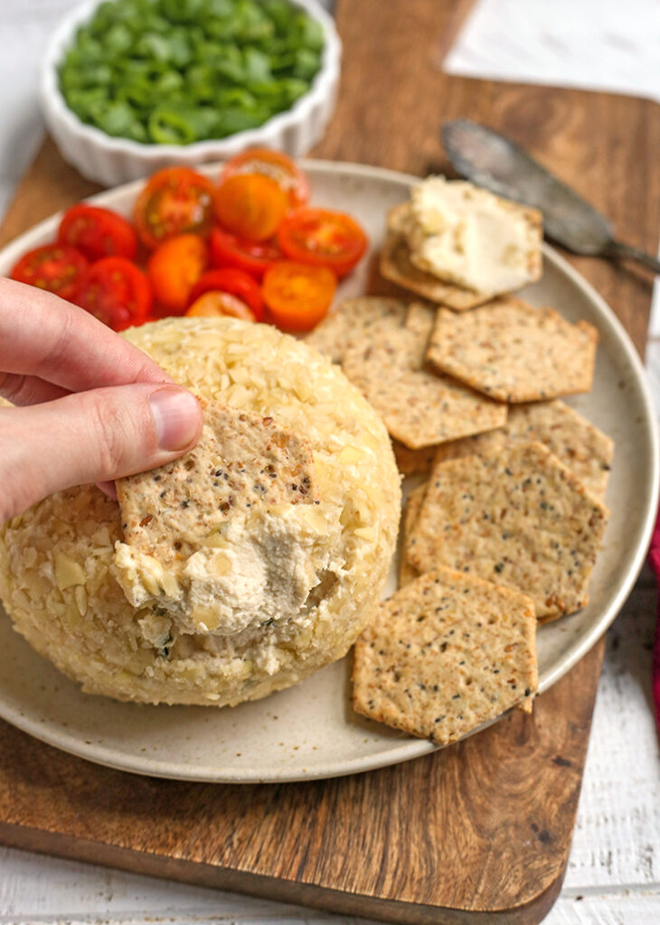 a hand dipping a cracker into a paleo vegan cheeseball