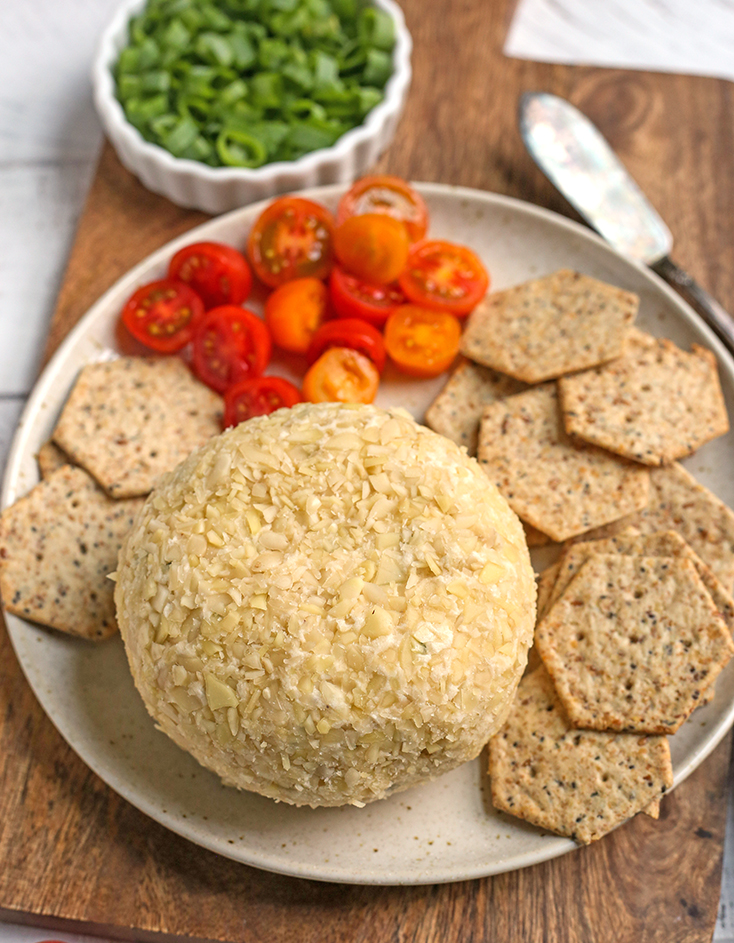 vegan paleo cheeseball on a plate with crackers