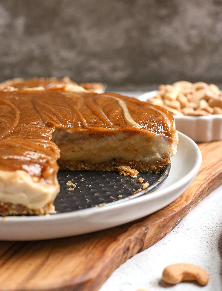 a paleo vegan cinnamon roll cheesecake with a slice missing