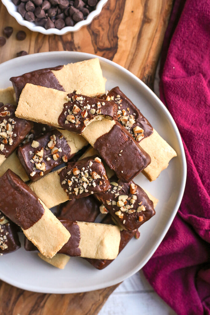 chocolate dipped grain free shortbread cookies stacked on a plate