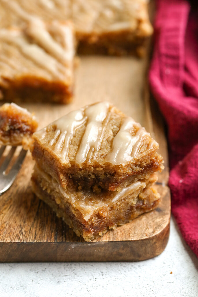 a stack of two paleo cinnamon roll blondies, a bite taken out of the top one