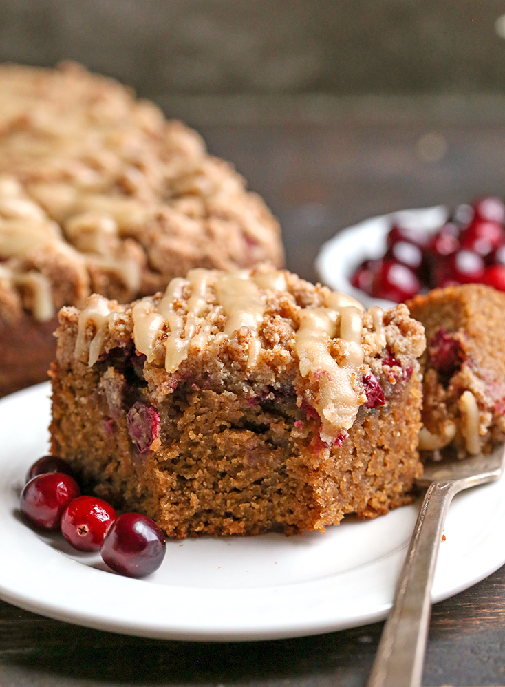 a close shot of a piece of grain free cranberry coffee cake with a bite taken out