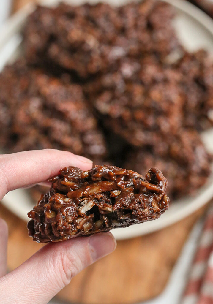 a hand holding a paleo nut free no bake cookie with a bite taken out
