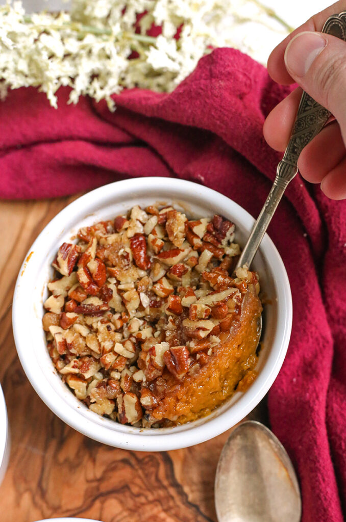 a spoon taking a scoop out of a paleo sweet potato pecan dessert cup