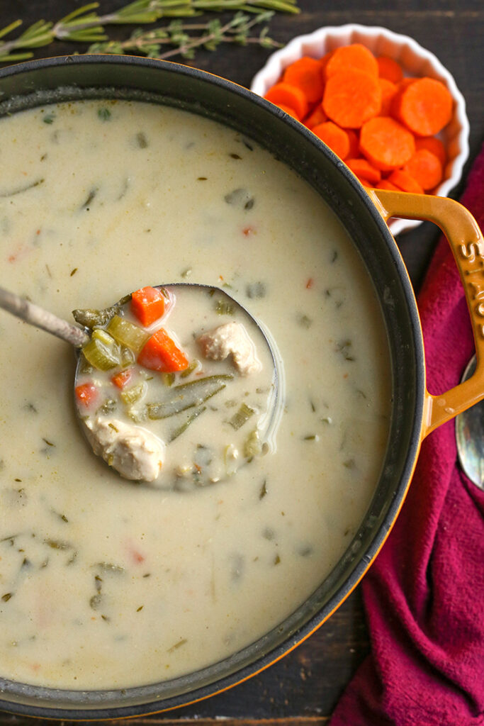 pot of paleo gluten free creamy chicken soup with a ladle taking a scoop