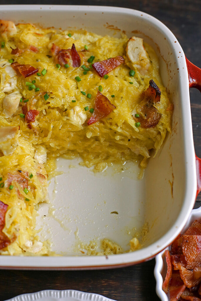 a pan of paleo whole30 chicken bacon ranch casserole with a serving removed so the layers are shown
