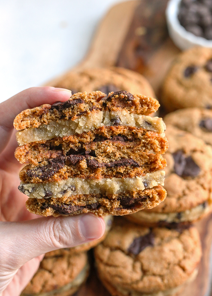 hand holding stacked paleo chocolate chip cookie dough sandwiches with the inside showing