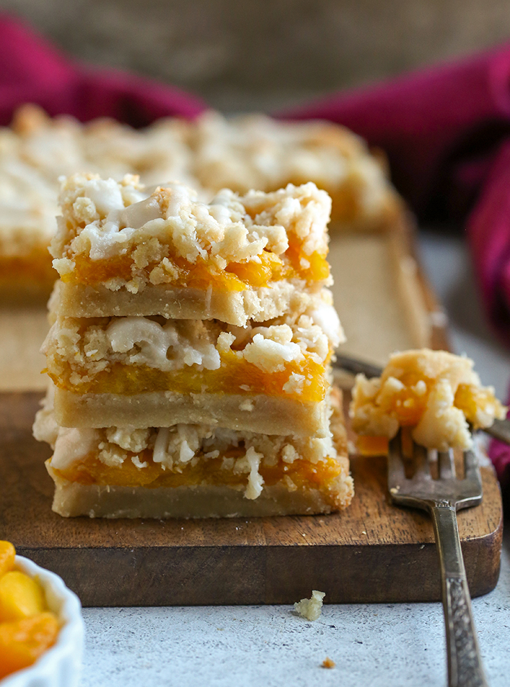 paleo vegan mango crumb bars in a stack with a bite taken out of the top one