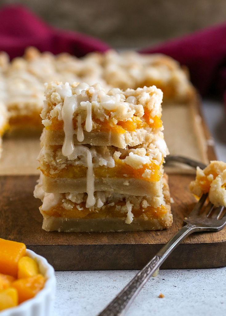 stack of paleo vegan mango crumb bars with a bite taken out of the top one, glaze dripping down