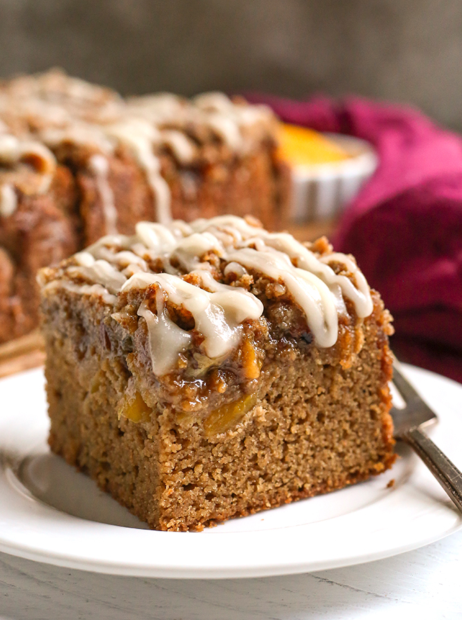 a piece of paleo peach coffee cake on a small plate with a fork