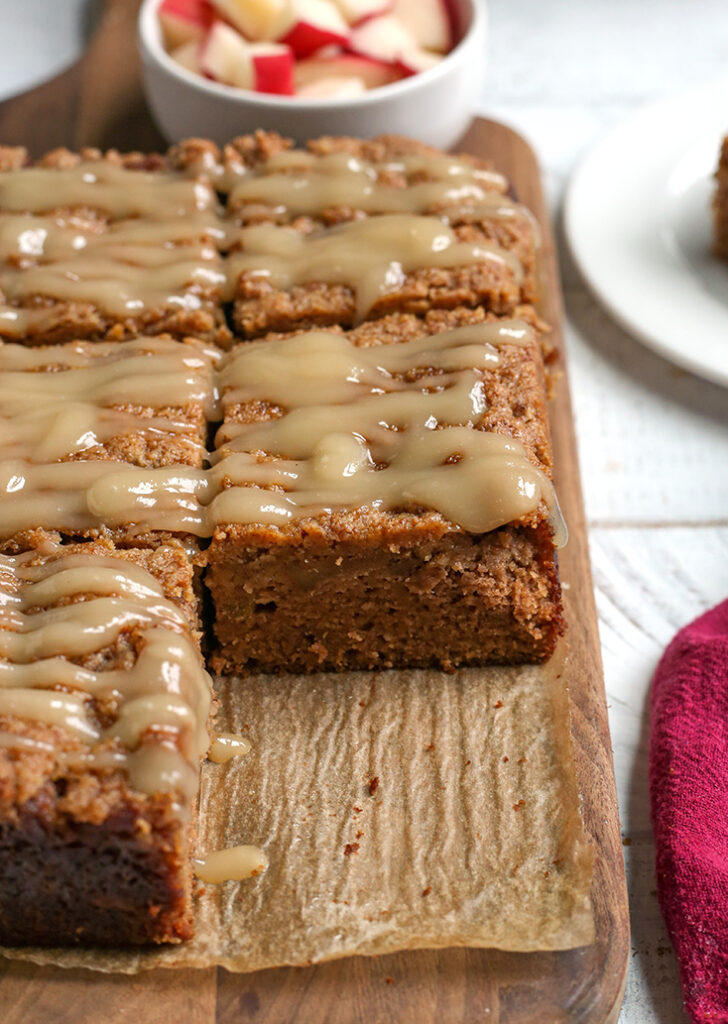 a cutting board with paleo apple crisp coffee cake on it, one piece removed