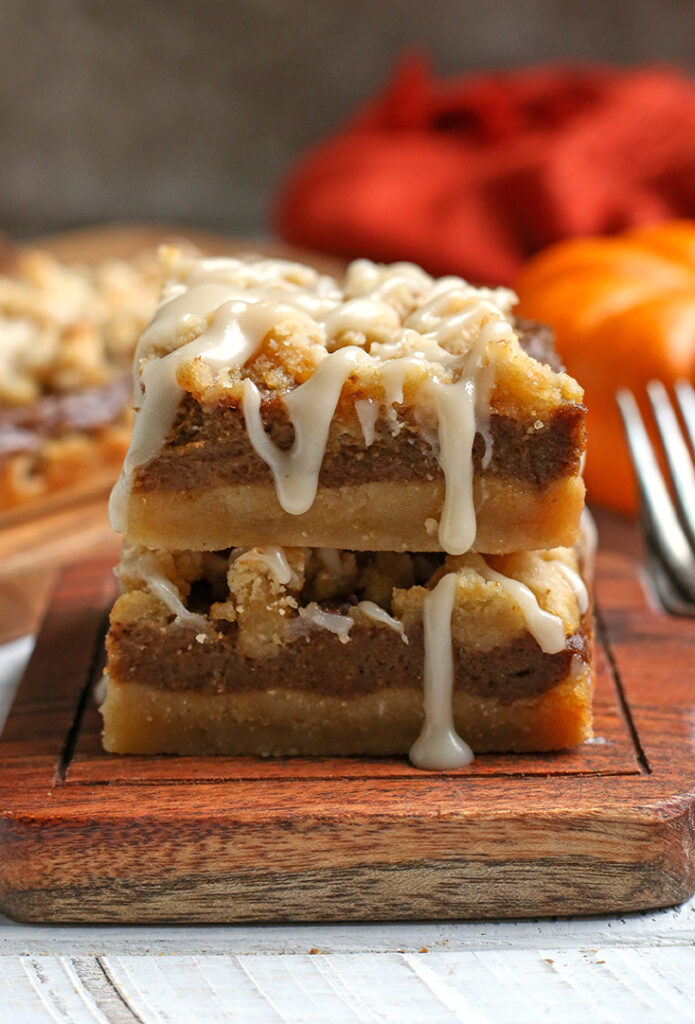 stack of paleo pumpkin crumb bars with glaze dripping down the side