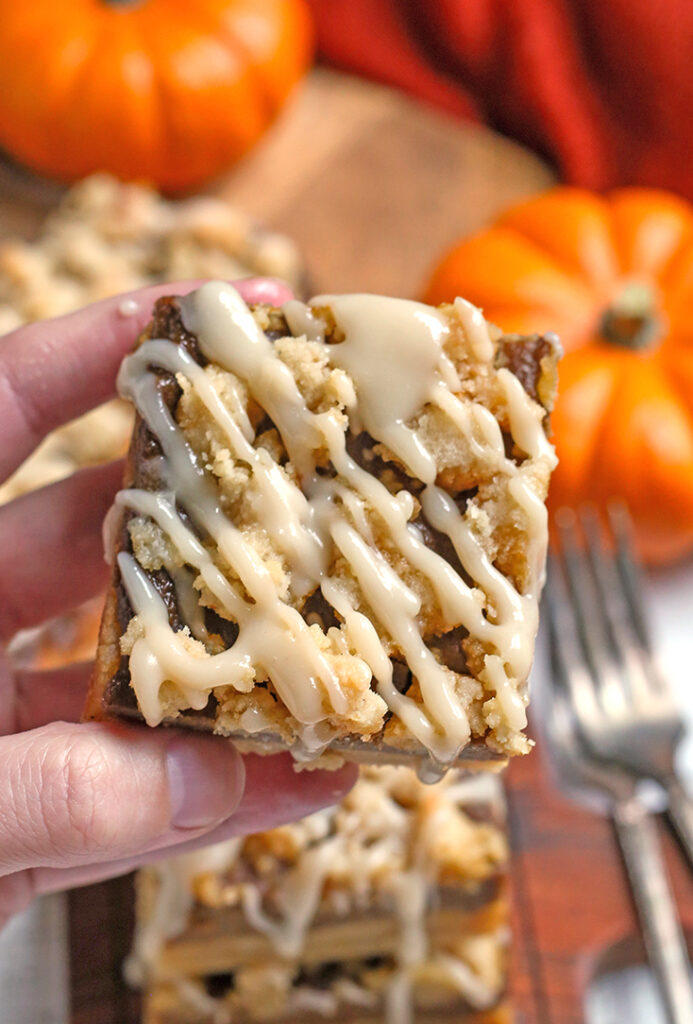 hand holding a paleo vegan pumpkin pie crumb bar with the top showing the crumb and glaze